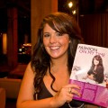 Chrissy Fogerty, Omaha Fashion Week intern, poses next to her magazine story