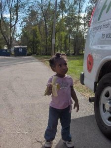Child enjoys banana delivered by Food Bank's Fresh Truck